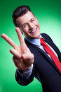 Business man in a suit giving the victory sign Stock Photos