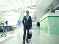 Business man with suitcase in hall of airport. Royalty Free Stock Photo