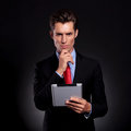 Business man with tablet thinking Royalty Free Stock Photo