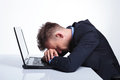 Business man takes a nap on laptop young taking with his head in his over his hands gray studio backgroud Royalty Free Stock Images