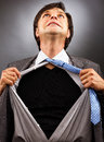 Business man tearing off his shirt over gray background Royalty Free Stock Images