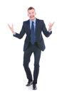 Business man tells a joke full length picture of young telling with his hands opened and with big smile on his face while looking Royalty Free Stock Image