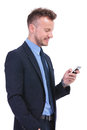Business man texting on his phone young and smiling while holding hand in pocket white background Royalty Free Stock Photo