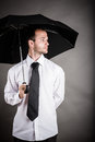 Business man with an umbrella in hand Stock Photos