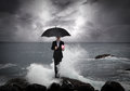Business man under an umbrella in the sea standing on a rock with lightning sky concept Royalty Free Stock Photo