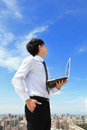 Business man using laptop and look to blue sky young cloud with cityscape in the background cloud computing Stock Photo