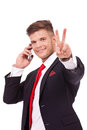 Business man victory sign young speaking on the phone and showing with a smile on his face isolated on white background Stock Image