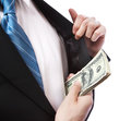 Business man with wad of cash in his jacket pocket putting a suit on white background Royalty Free Stock Photos