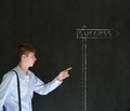 Business man walking pointing down chalk success road street sign blackboard background Stock Photos
