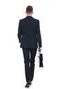 Business man walks away with suitcase full length rear view picture of a young walking from the camera a in his hand on white Royalty Free Stock Photography