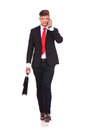 Business man walks with brief phone full length picture of a young walking towards the camera a brirefcase while speaking on the Royalty Free Stock Image