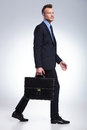 Business man walks with suitcase in hand full length portrait of a young walking to the side and looking away from the camera Royalty Free Stock Photography