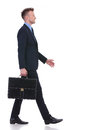 Business man walks to side with briefcase full length view picture of a young walking a suitcase in his hand and a smile on his Stock Images