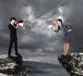 Business man and woman shouting to each other through megaphone on danger precipice on the mountain with rainstorm clouds Royalty Free Stock Image
