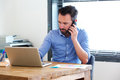 Business man working on laptop and talking on mobile phone Royalty Free Stock Photo