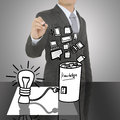Business man writing concept of Paper light bulb and knowledge battery Royalty Free Stock Photo