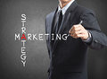 Business man writing marketing strategy concept by crossword Royalty Free Stock Images