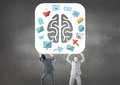 Business mans carrying the brain with the graphic about purchasings and sales Royalty Free Stock Photo
