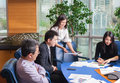 Business meeting asian nationality people sitting for a glass table with plan on high floor in the office male in Royalty Free Stock Image