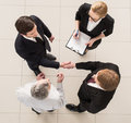 Business meeting top view of four people in formalwear standing close to each other while two of them handshaking Royalty Free Stock Images