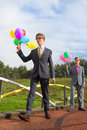 Business men with balloons outdoor on a bridge Stock Photo