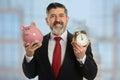 Business metaphor of time is money hispanic senior businessman holding piggy bank and clock to represent Stock Photos
