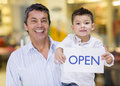 Business owner and son holding an open sign Stock Photos