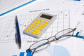 Business papers with graphs charts glasses pen and calculator on the table Stock Photos