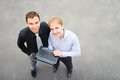 A business partners looking at the camera on the street image of and using laptop focus is made top of gray background of Stock Images