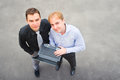 A business partners looking at the camera on the street image of and using laptop focus is made top of gray background of Stock Photography