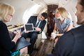 Business partners meeting in private plane businessman showing project on digital tablet to Stock Photos