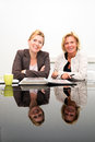Business partners portrait of two senior women acting as in a small firm sitting at a black glass table their smiling reflections Stock Photo