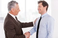 Business partners two cheerful men shaking hands and looking at each other Stock Image