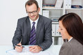 Business partners at work in the office with focus over shoulder of a women to a smiling confident businessman glasses Royalty Free Stock Image