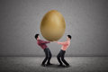 Business partnership carry golden egg two businessmen holding big on grey background Stock Images