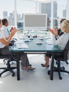 Business people applauding during a video conference while they are sat in the boardroom Royalty Free Stock Image