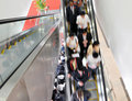 Business people on the escalator Stock Images