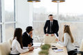 Business people in formalwear discussing with leader something while sitting together at the table Royalty Free Stock Photo