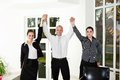 Business people with hands up in office Stock Image