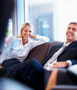 Business people having fun while sitting on sofa Royalty Free Stock Photo