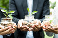 Business people holding glass jars with plants growing from mone Royalty Free Stock Photo
