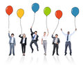 Business people holding multicoloured balloons playful Royalty Free Stock Photo