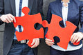Business people holding red jigsaw two two big puzzle pieces Royalty Free Stock Photography