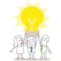 Business people holding up huge light bulb Royalty Free Stock Images