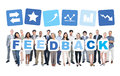 Business people holding word feedback multi ethnic group of and casual cardboard forming Stock Photography