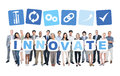 Business people holding the word innovate multi ethnic group of and casual cardboards forming and related symbols above Stock Images