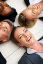 Business people lying in a circle on the floor Royalty Free Stock Photo