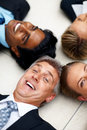 Business people lying in a circle on the floor Stock Images