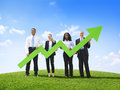 Business people outdoors holding developed line graph Royalty Free Stock Image