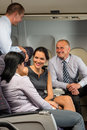 Business people passengers flying airplane talking travel flight cabin Stock Image